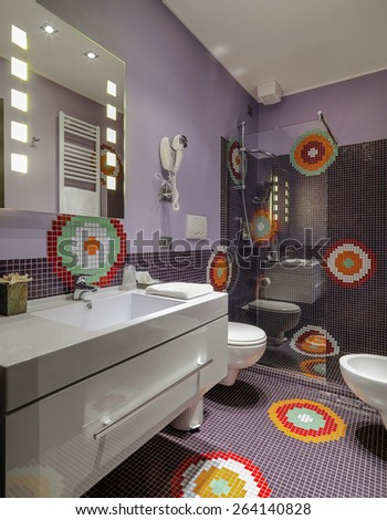 interior view of a modern bathroom with colored mosaic tiles, foreground of washbasin overlooking on the  shower cubicle - stock photo