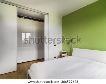 interior view of a modern bedroom with wood floor whose wall is painted of green overlooking on the corridor   - stock photo