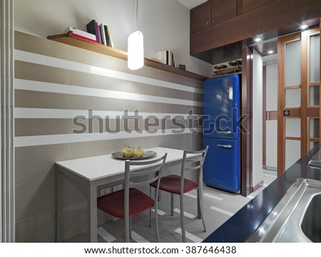 interior view of a modern kitchen in foreground the dining table with plat of pears on the itself and the blue fridge - stock photo