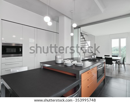 interior view of a modern kitchen with kitchen island overlooking on the dining room - stock photo