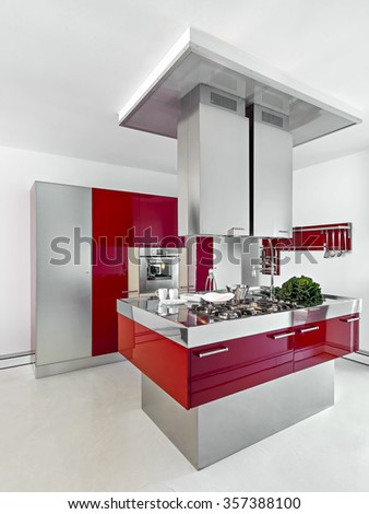 interior view of a modern kitchen with red furniture in foreground the kitchen island whose floor is made of resin