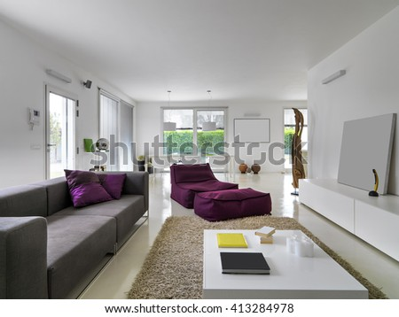interior view of a modern living room total white in foreground the sofa and purple armchair - stock photo