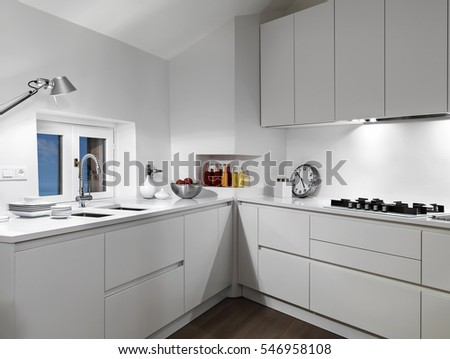 interior view of a white  modern kitchen in the mansard with wood floor