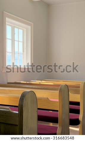Interior view of an old church with empty pews - stock photo