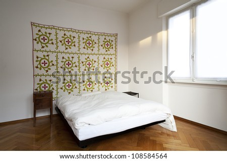 interior white bedroom, decorative carpet on the wall - stock photo