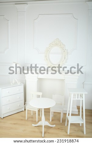 Interior white room with columns in ancient style, a fireplace and openwork frame, round table and chairs, commode and lamp  - stock photo