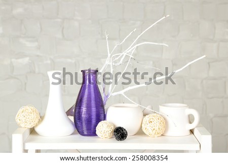 Interior with decorative vases and branch twig on table top and white brick wall background - stock photo