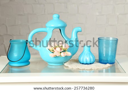 Interior with decorative vases and small roses on table top and white brick wall background - stock photo