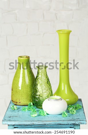 Interior with decorative vases on nightstand and white brick wall background - stock photo