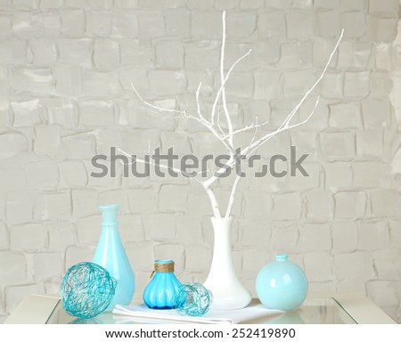 Interior with decorative vases on table top and white brick wall background - stock photo