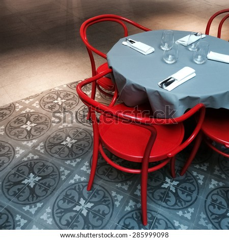 Interior with round dining table and red chairs. - stock photo