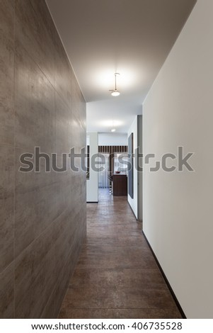 Interiors of new apartment, long corridor with marble wall  - stock photo
