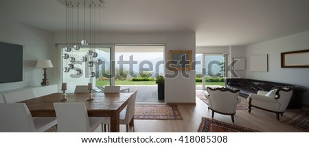 Interiors of new apartment, wide living room with old dining table - stock photo