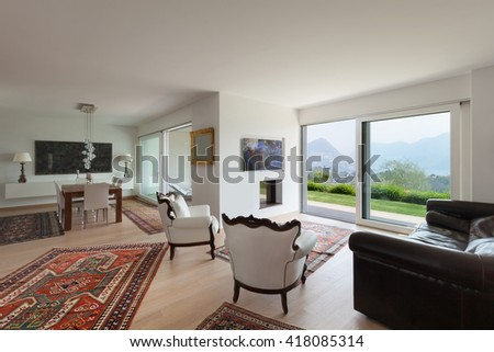 Interiors of new apartment, wide living room with white armchairs - stock photo