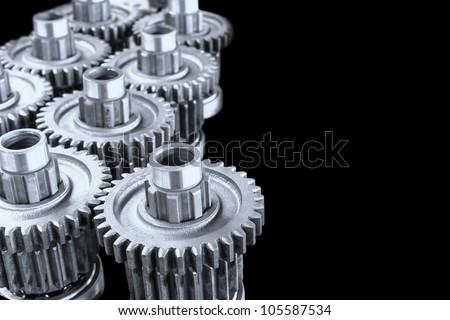 Interlocking industrial metal gears on black background - stock photo