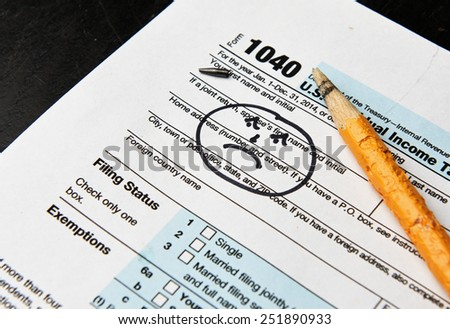 Internal Revenue Service form 1040 with chewed pencil & sad face drawn in upper left corner