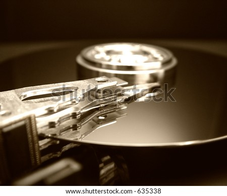 Internal workings of a hard drive in a gold tone color - stock photo