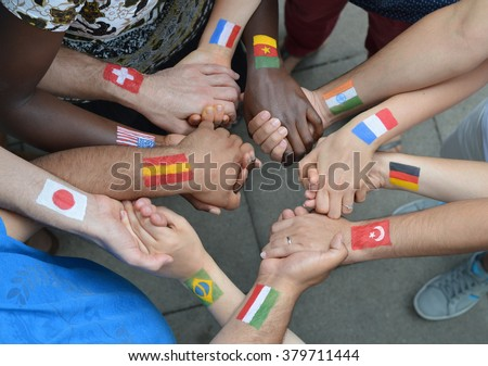 International brothers and sisters with different flags painted on their arms standing in a circle together and holding hands. - stock photo