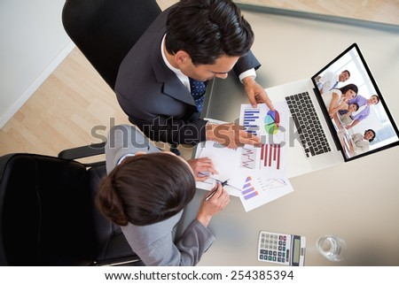 International business associates in a meeting against sales persons studying statistics - stock photo