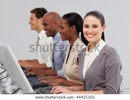 International business people in a line working at computers in the office