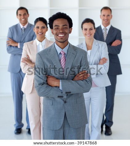 International business team standing in office looking at the camera - stock photo
