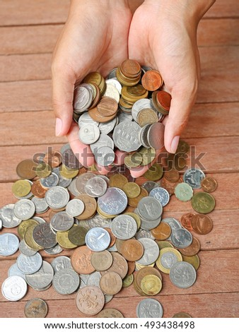 International coins full female hand on wood plank background