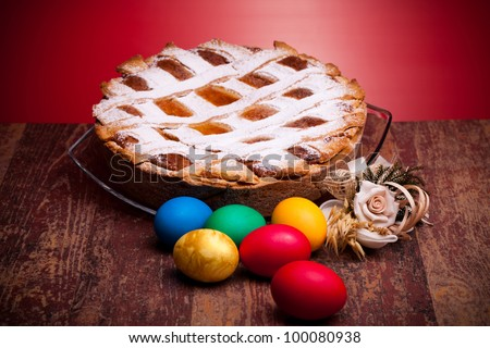 International Cuisine - Desserts - Neapolitan Pastiera and colorful Easter eggs. Pastiera is a wheat and ricotta pie that is also known as Pizza Gran. - stock photo