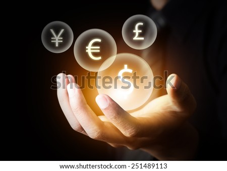 International currencies (US Dollar, Euro, Pound sterling, Japanese Yen) on businessman's hand