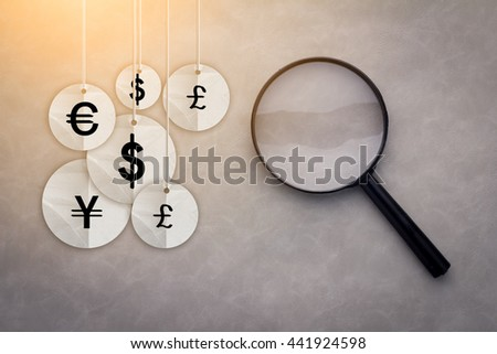 International economy icons under the magnifying glass business financial concept - stock photo