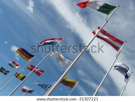 International flags flutter in blue cloudy sky