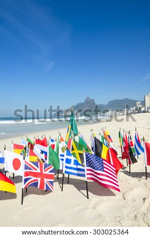 International flags fly with Brazilian flag on the sand against a skyline view of Ipanema Beach in Rio de Janeiro, Brazil