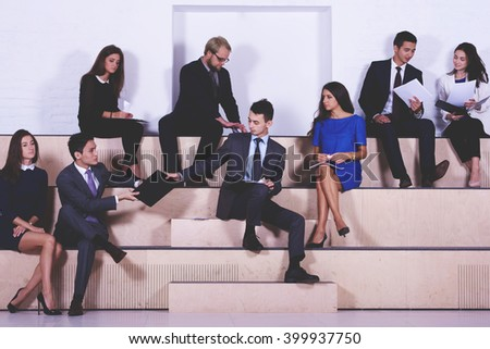 International group of a young managing directors are making the a business plan for next year by using paper documents with confidential information company work,while are sitting in co-working space - stock photo