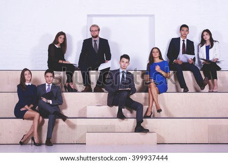 International group of professional workers with paper documents in hands are waiting the beginning of the interview. Entrepreneurs are posing after analysis of activity of their joint venture company - stock photo