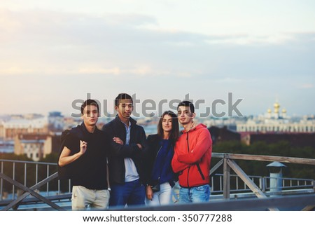 International group of young people posing while standing on a building roof against beautiful city landscape and evening sky, friends dressed in stylish clothes enjoying free time during vacations  - stock photo