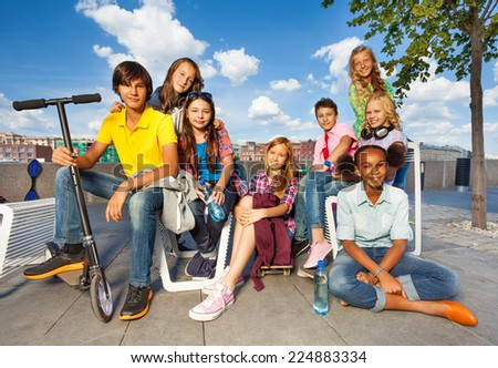 International kids sitting on chairs with scooter