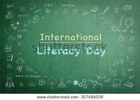 International literacy day text message on black chalkboard with doodle freehand sketch chalk drawing: Announcement on literacy campaign concept to school teachers, student and the world - stock photo
