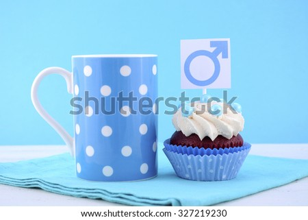 International Mens Day Cupcake with Male Symbol with pale blue polka dot coffee mug on blue and white wood background. - stock photo