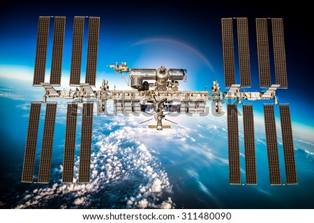International Space Station over the planet earth. Elements of this image furnished by NASA. - stock photo