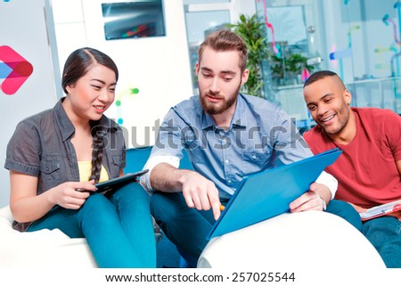 International team. Group of cheerful students in smart casual discussing something in teamwork while sitting in creative space  - stock photo