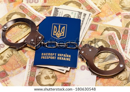International Ukrainian passport with US dollars and handcuffs on Hryvna banknotes background - stock photo