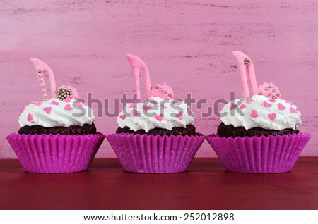 International Womens Day, March 8, cupcakes with high heel stiletto fondant shoes on vintage pink wood background.