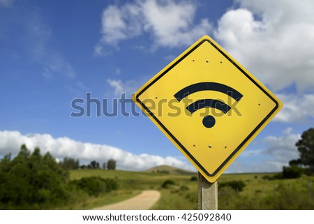 Internet access in remote zone, power of technology concept. Road sign with wifi signal icon on rural environment, includes copy space.  - stock photo