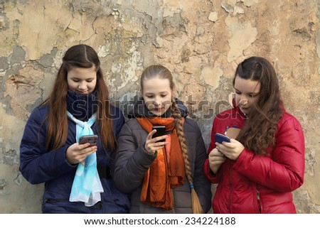 Internet and social networks replace live communication. Three girls together chat using their smartphones outdoor - horizontal - stock photo