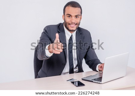 Internet banking for business. Successful African businessman sitting at a laptop and holding credit card in hand until businessman doing orders through the Internet showing a thumbs up - stock photo