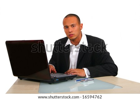 Internet Business A young businessman sitting by desk at office working on the laptop with cellphone on the table. Isolated over white. - stock photo