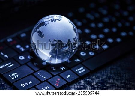 Internet concept. Closeup of glass globe on laptop keyboard - stock photo