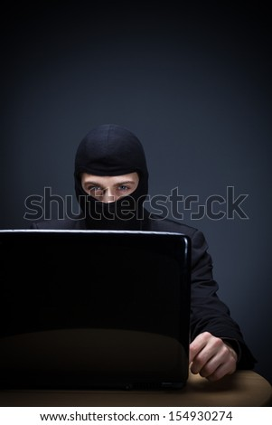 Internet criminal or hacker dressed in black clothing and a balaclava sitting behind a laptop computer stealing personal identities or business information and data over a dark background