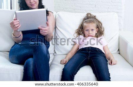 internet network addict mother using digital tablet pad ignoring little sad daughter left alone bored and depressed feeling abandoned and disappointed with mum in parent bad selfish behavior - stock photo