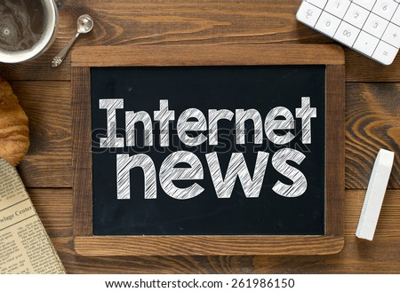 Internet news handwritten on blackboard. Internet news Handwritten with white chalk on a blackboard, cup of coffee ,croissant, newspaper and calculator on wooden background - stock photo