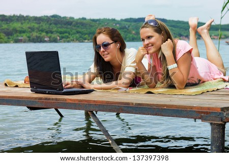 Internet on holidays / Two cheerful young woman use a laptop on holidays - stock photo